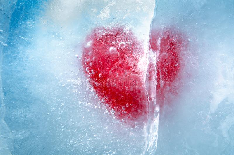 Red heart frozen in ice with a big crack, a symbol of love or betrayal or separation. Studio photography royalty free stock photo