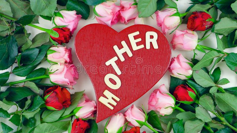 Red heart gift box surrounded by pink and red roses for Mother`s Day overhead. royalty free stock images