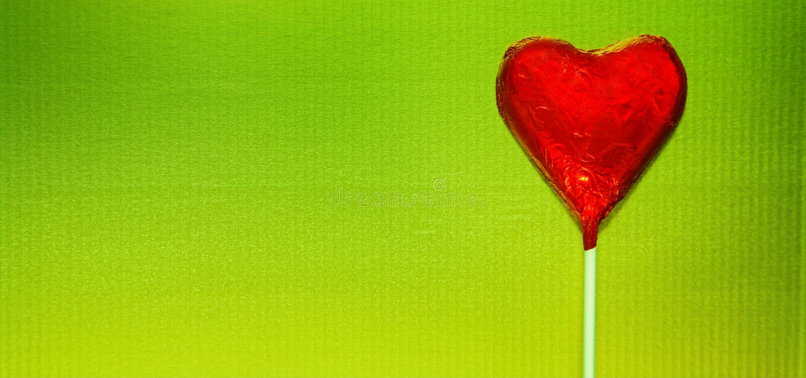 Red heart on green. Red candy heart on bright golden green background stock photography