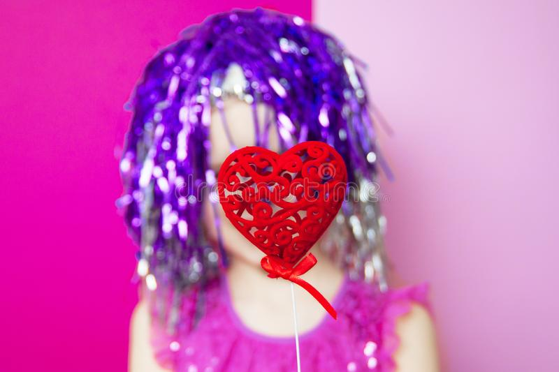 Red heart in hands happy little girl with purple hair on pink Background. selective focus - Valentines and 8 March Mother Women. `s Day concept royalty free stock image