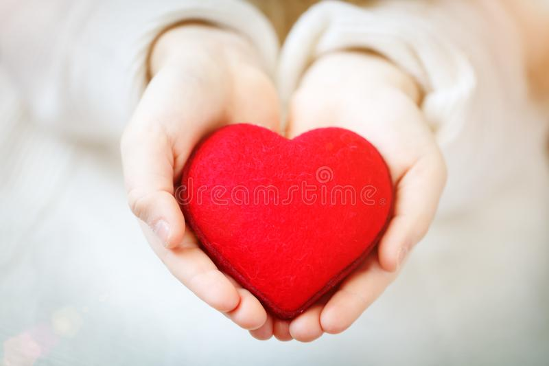 Red heart in hands of the little girl. Symbol of love and family.Valentines day card. Mother`s day. Backgrounds for. Social posters. Selective focus. Background royalty free stock photography