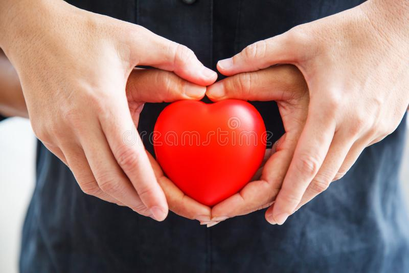 Red heart held by male and female`s both hands, represent helping hands, help each other, love, partnership, sympathy, customer an. D patient assistance, support royalty free stock image