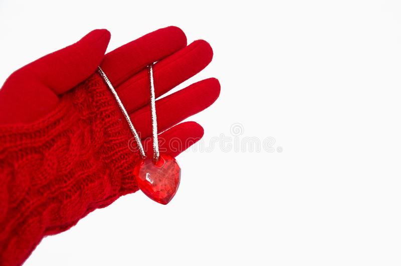 Red heart lies on the palm of the hand in a red glove. Image royalty free stock photos