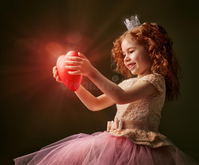 Red heart. Little girl holding a heart