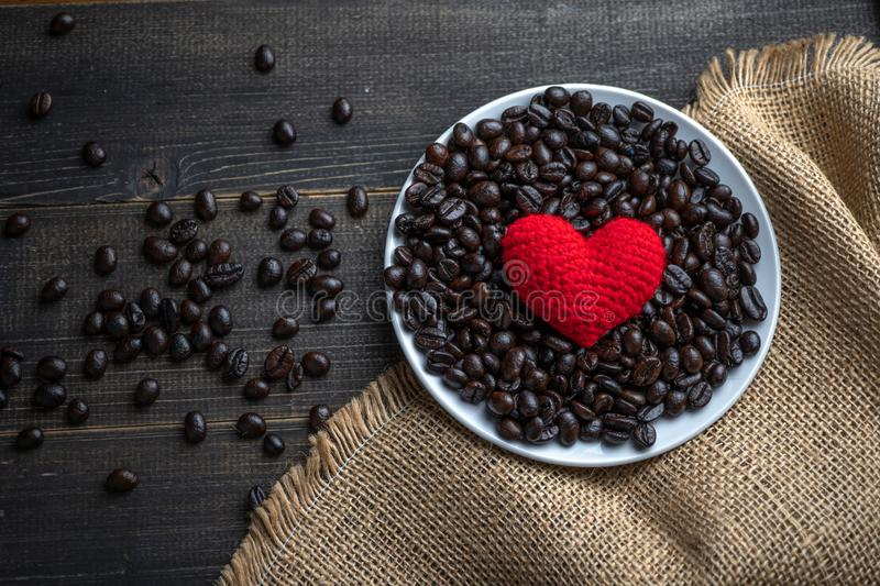 Red heart on a lot of roasted coffee beans background on white plate on wooden table. Strong black espresso, Grains of coffee back stock images