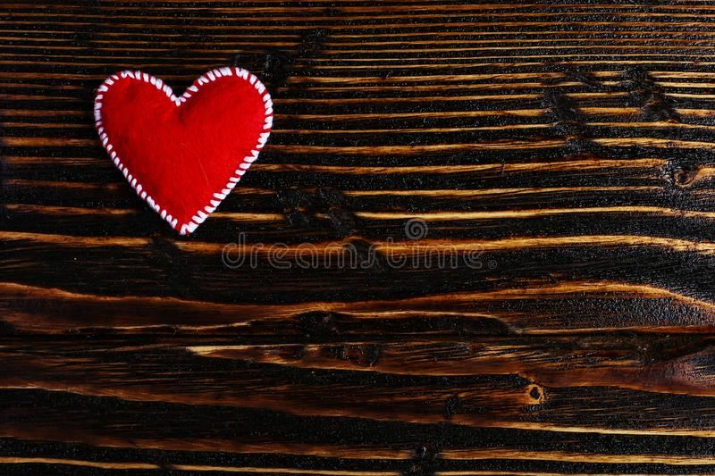 Red heart made of felt on a wooden table. Handmade blank for greeting card, copy space stock image