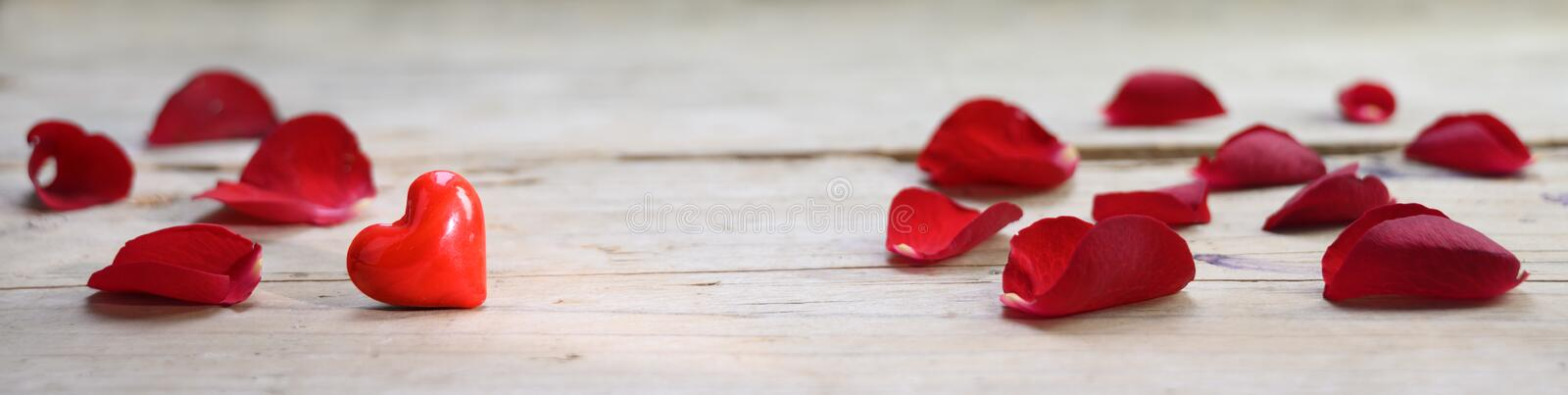 Red heart made from glass and rose petals on a rustic wooden board, love concept with copy space, in panoramic banner format. Selected focus, narrow depth of stock photo