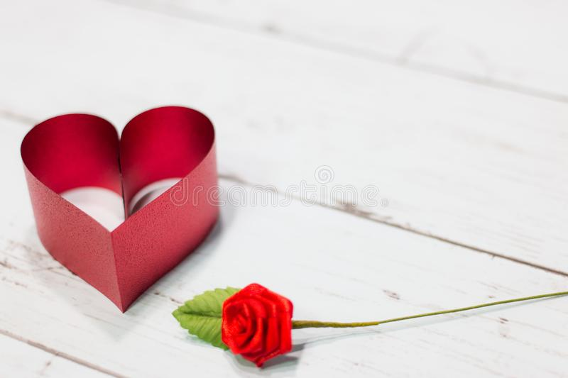 Red heart made of ribbon with rose on a wooden background using as love, valentine day concept. stock images
