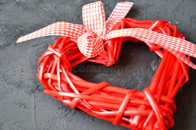 a red heart made of wood texture. A celebration of love. Valentine's day. wicker red heart with bow and ribbon on black backgroun royalty free stock photos