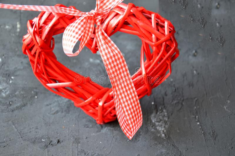 a red heart made of wood texture. A celebration of love. Valentine's day. wicker red heart with bow and ribbon on black backgroun stock photography