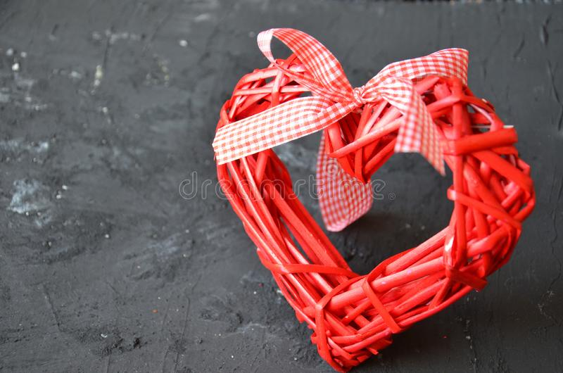 a red heart made of wood texture. A celebration of love. Valentine's day. wicker red heart with bow and ribbon on black backgroun stock photos