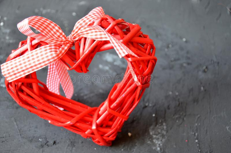 a red heart made of wood texture. A celebration of love. Valentine's day. wicker red heart with bow and ribbon on black backgroun royalty free stock photography