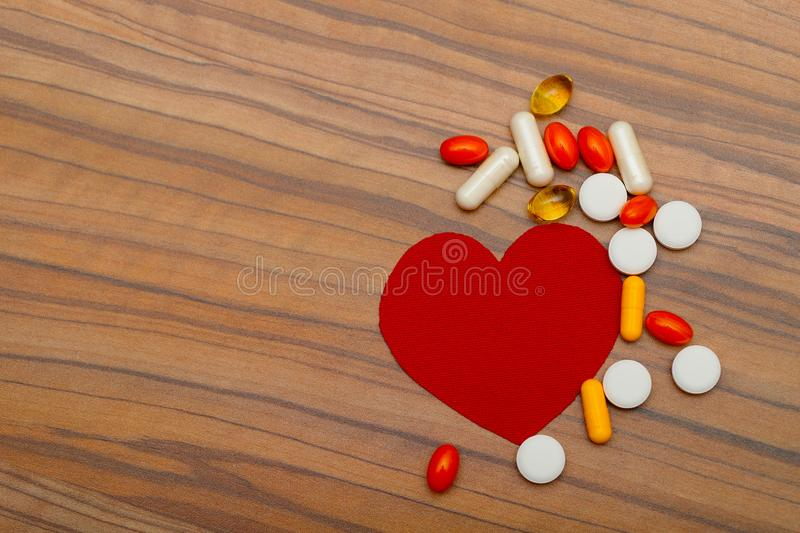 Red heart and many bright pills drugs on wooden background. royalty free stock photography