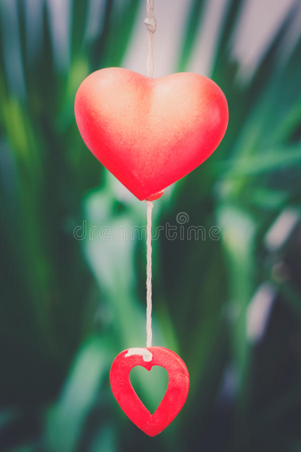 Red heart. Model for decoration over a green leaves out of focus background of leaves, vintage tone stock photography