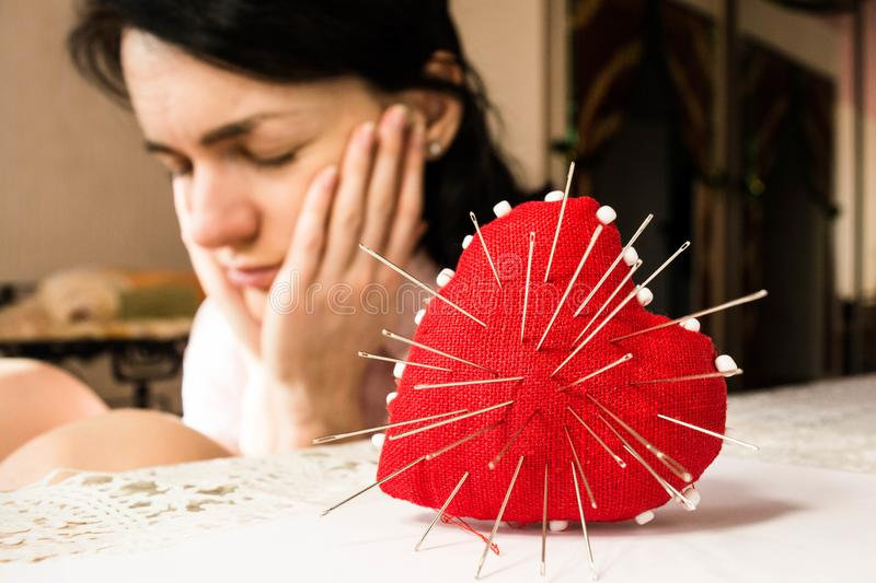 Red heart with needles and young upset woman, selective focus royalty free stock image