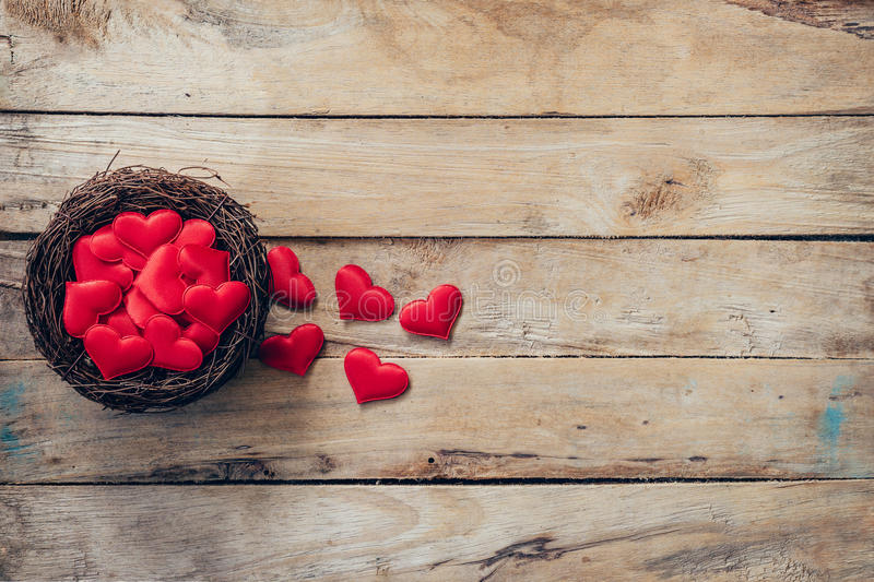 Red heart in the nest on wood background with space stock photography