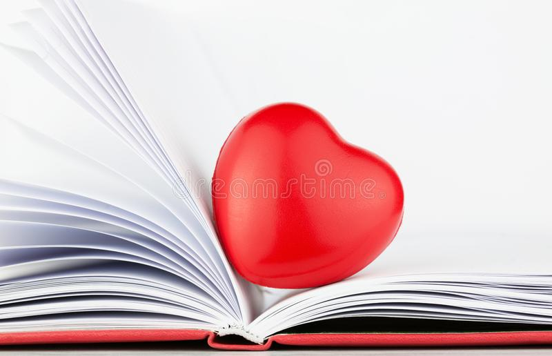 Red heart on the open book with red cover. Whete sheets stock images