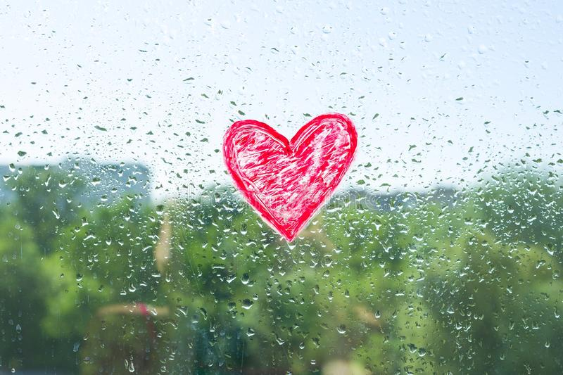 Red heart painted with lipstick on the window with water drops. Background blue sunny sky, drops shine in the sun. royalty free stock photo