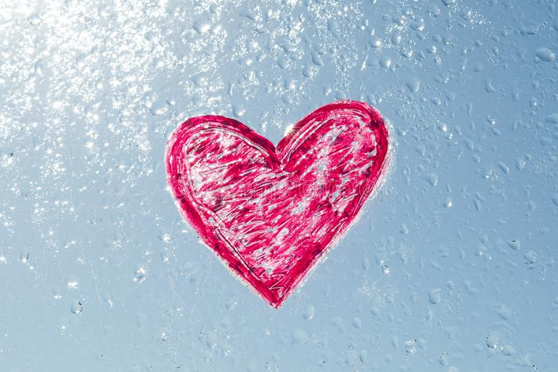 Red heart painted with lipstick on the window with water drops. Background blue sunny sky, drops shine in the sun royalty free stock photo