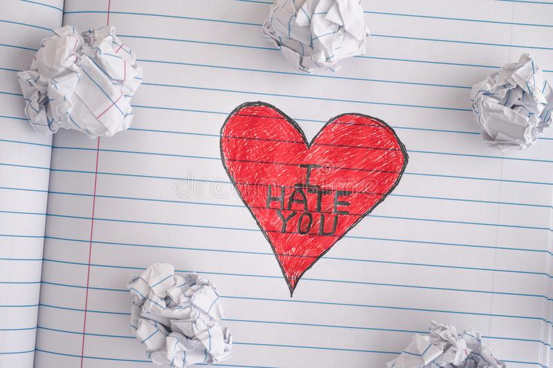 Red Heart with phrase I Hate You. I Hate You. Red Heart with phrase I Hate You on notebook sheet with some crumpled paper balls on it. Close up royalty free stock photography