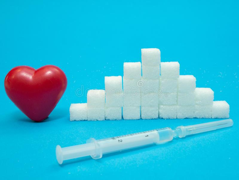 Red heart, pile of white sugar cubes, syringe with insulin royalty free stock photography