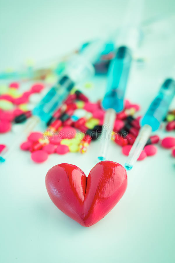 Red heart with pills and injection background royalty free stock images