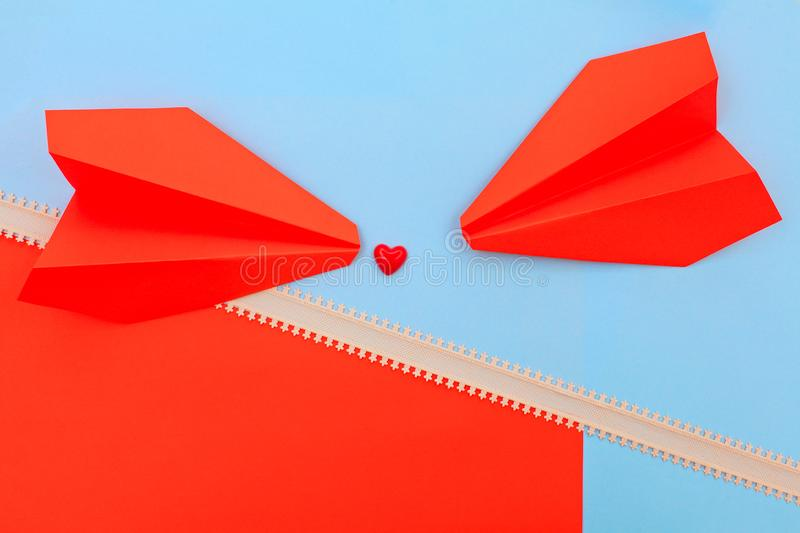 Red heart on the pink and blue background with arrow line and paper airplanes royalty free stock photography