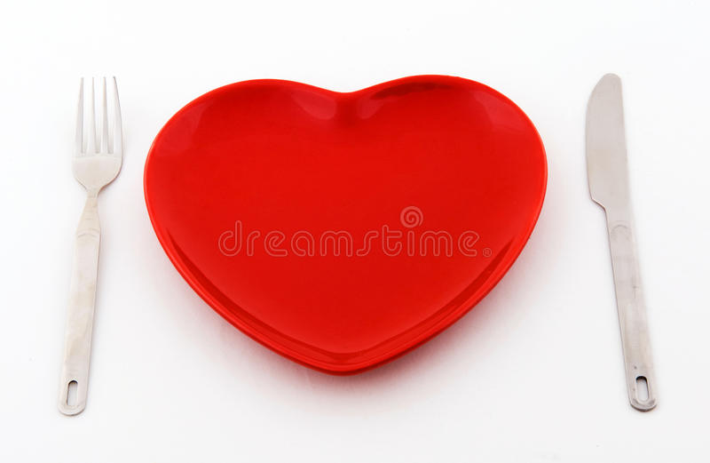 Red heart plate. Empty red heart plate with knife and fork on a white background royalty free stock photos