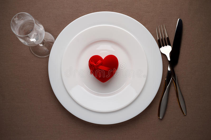 Red heart on a plate for romantic date on Valentines day. Top view stock image