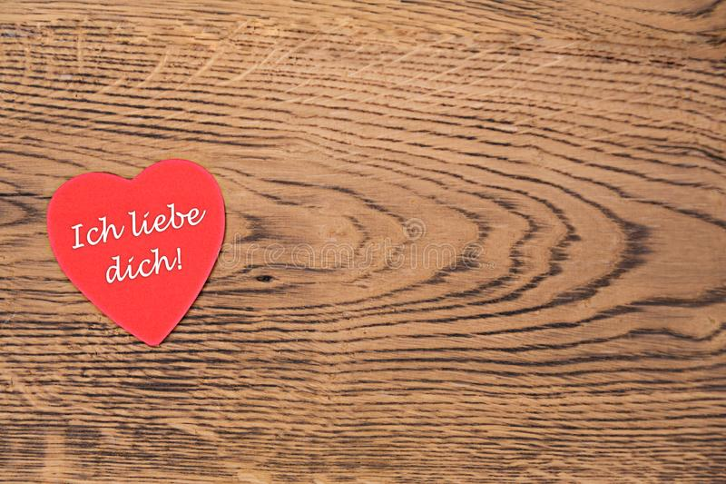 Red heart post-it with the text `Ich liebe dich` on a wooden background. Translation: `I love you`. Red heart post-it with the white text `Ich liebe dich` on a stock photos