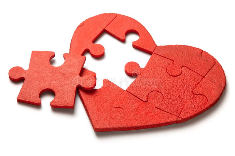 Red heart puzzle on white background. Concept second half of the heart in love for Valentine`s Day or illness stock image
