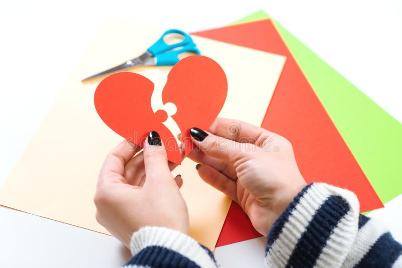 Red heart puzzle. Woman hands holds two part of paper heart. Happy Valentine`s day. Be in love. Female hand matching red puzzle stock photo