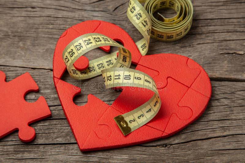 Red heart puzzle and yellow measuring tape. Overweight kills the heart. Concept Obesity royalty free stock photos