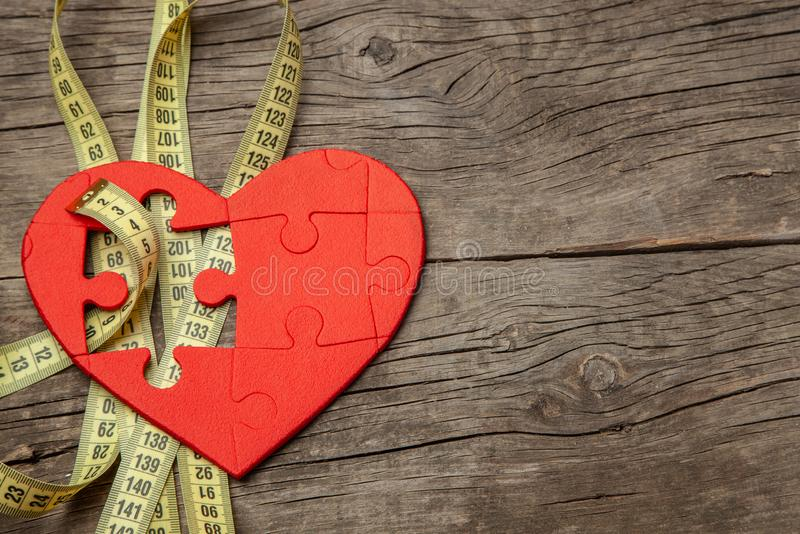 Red heart puzzle and yellow measuring tape. Overweight kills the heart. Concept Obesity. Copy space for text stock photos