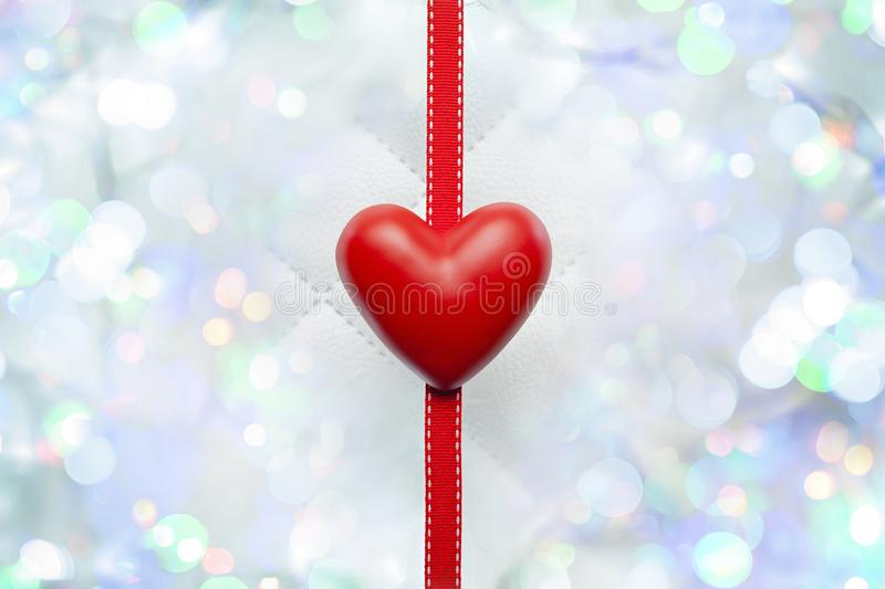 Red heart and ribbon on white leather and light bokeh effect background stock illustration