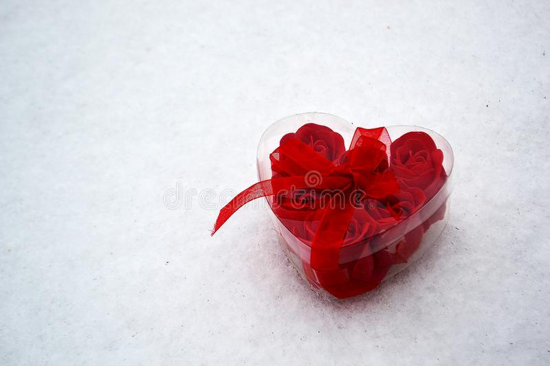 Red heart with roses inside in the snow. A gift for loved ones royalty free stock photo