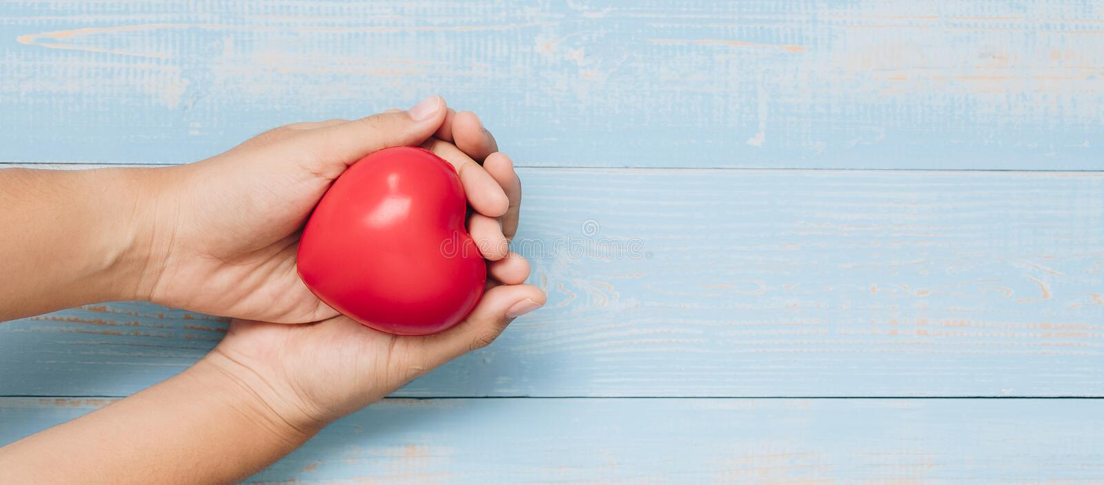 Red heart shape on pastel color wooden background. healthcare, organ donation, and insurance or Love and Valentine Day Concept. Top view hand holding red heart royalty free stock image