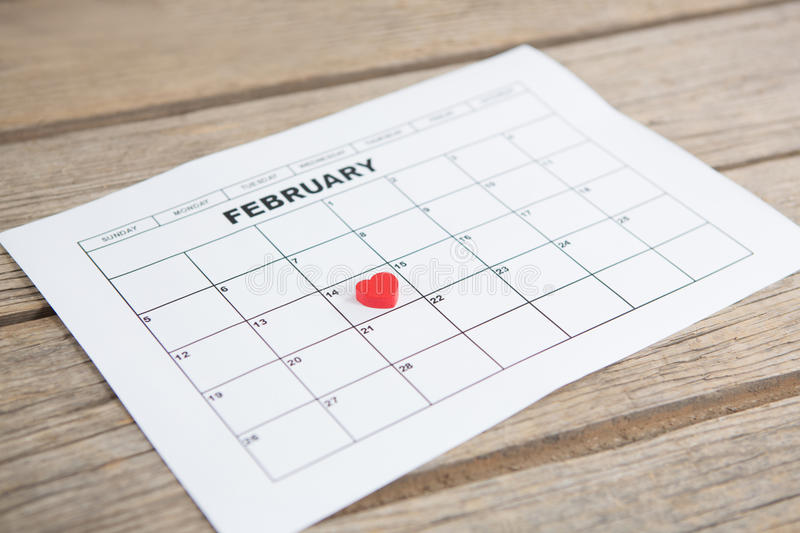 Red heart shape placed on 14th february date of the calendar. On wooden background stock photo