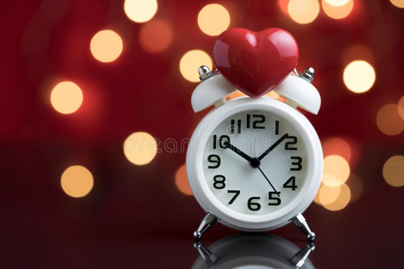 Red heart shape on top of white alarm clock with party decoration light bokeh in the red background using as time for love or royalty free stock image