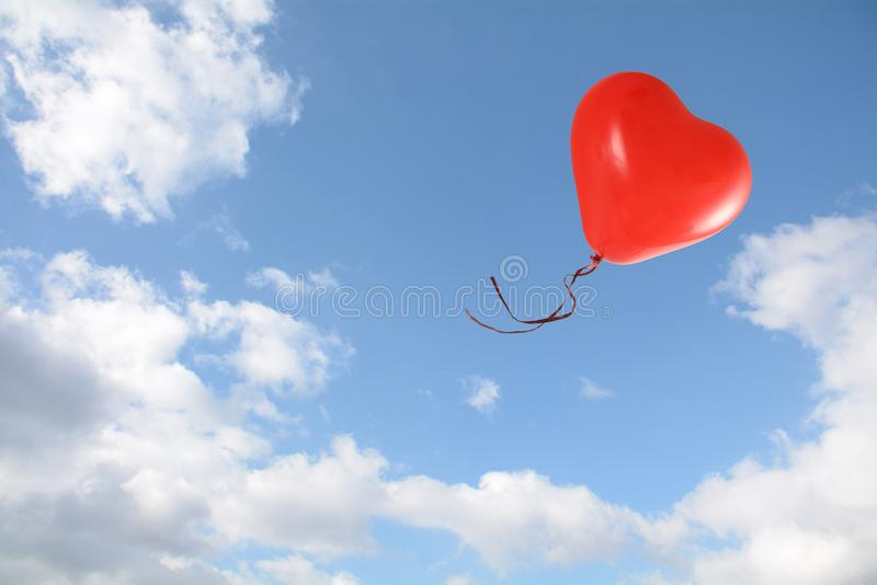 Red heart shaped balloon flies into the blue sky with clouds, love concept, copy space royalty free stock photo
