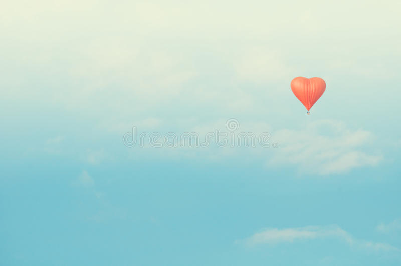 Red heart shaped balloon flying in the sunny sky. Vintage tones correction. royalty free stock photos