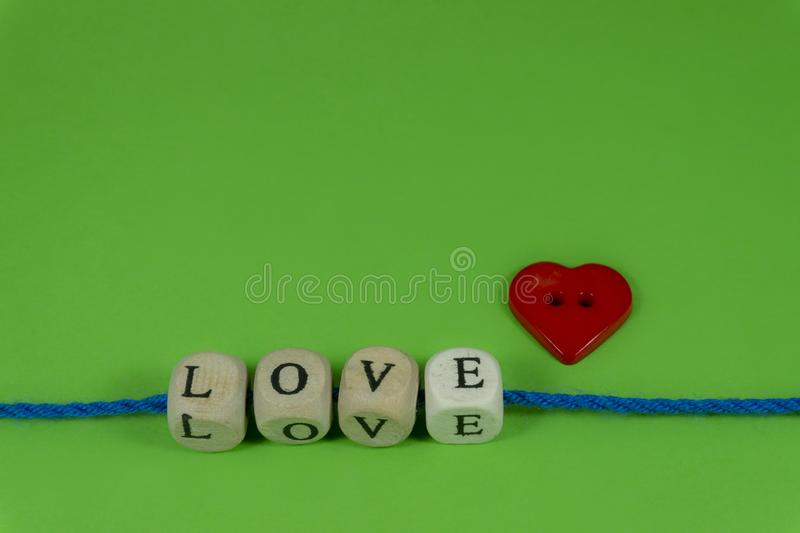 Red heart shaped button and word Love on blocks stock photos