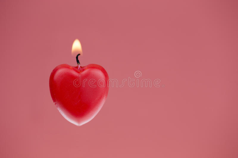Red heart shaped candle burning, pink textured background stock photography