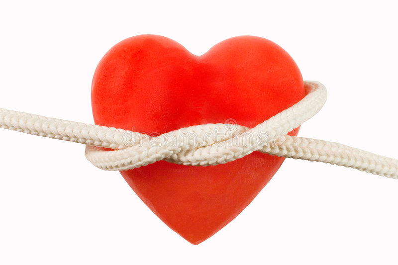 Red heart-shaped candle and a rope. Red heart-shaped candle (symbolizing a human heart) and a rope royalty free stock photos