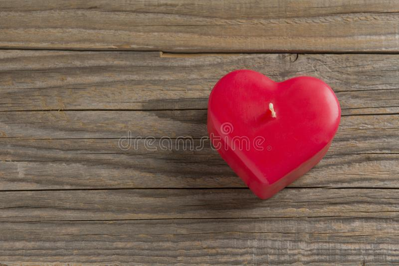 Red heart shaped candle on a wooden surface royalty free stock photo