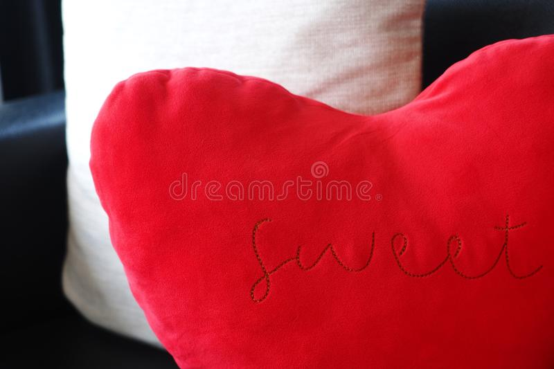 Red heart shaped cushion with sweet word stock photo