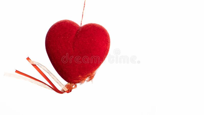 A red heart shaped hanging on a white. Background stock photo