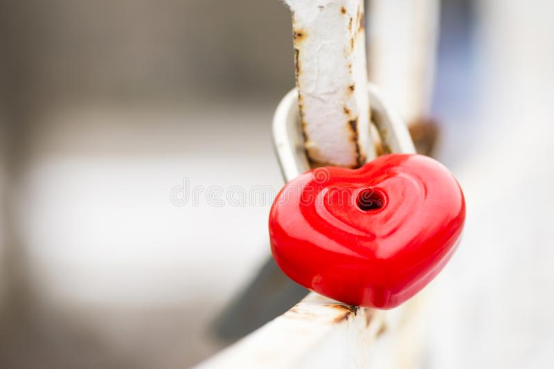 Red heart-shaped lock on bridge. Love locks on bridge. Lock in the shape of a heart. The closed red padlock in the form of heart stock images
