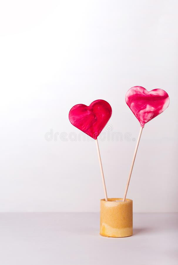 A red heart-shaped lollipops on a white background. Postcard to the day of St. Valentine. stock image
