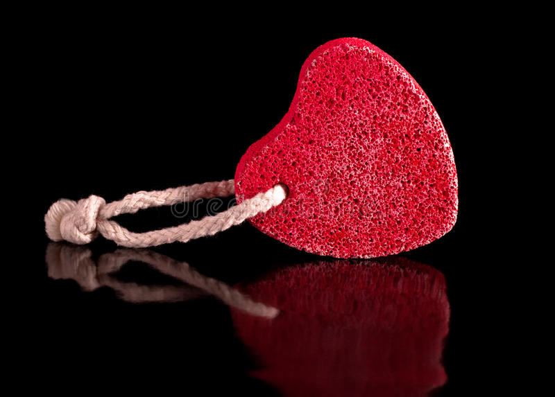 Red heart-shaped stone with rope